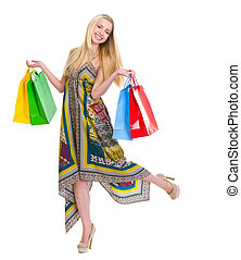 Happy girl in dress holding shopping bags