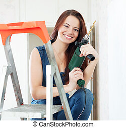 Happy girl in dungarees with drill