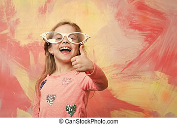Happy girl in funny eyeglasses giving thumbs up