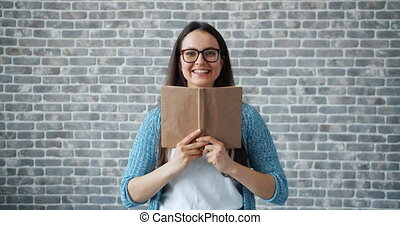 Happy girl in glasses reading book then smiling on brick wall background