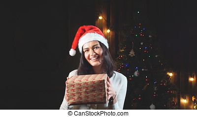 Happy girl in hat of Santa Claus with a gift in hand. Slow motion