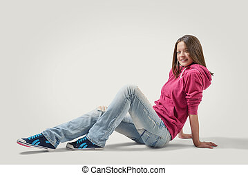 Happy girl in jeans and hoodie sits leaning back on her hands