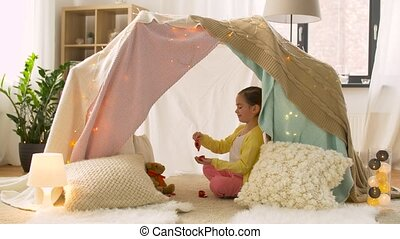 happy girl in kids tent playing tea party at home -...