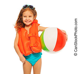 Happy girl in lifejacket with colored rubber ball