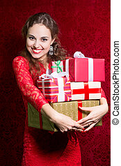 Happy girl in red dress with gift box.