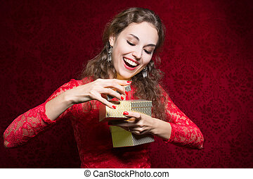 Happy girl in red dress with gift box