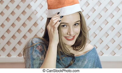 Happy girl in santa hat posing on background. Slowly