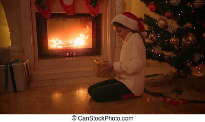 Happy girl in Santa hat sitting by the fireplace and looking inside glowing present box