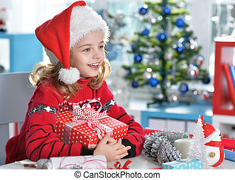 Happy girl in Santa hat sitting with Christmas present