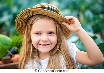 Happy girl in straw hat on cabbage field