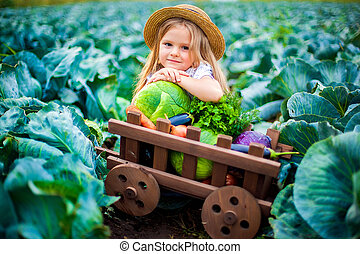 Happy girl in straw hat on cabbage field with basket of vegetables