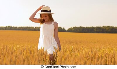 happy girl in straw hat walking along cereal field - nature,...