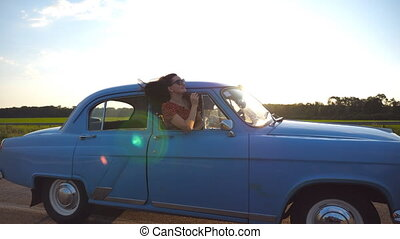 Happy girl in sunglasses leaning out of retro car window and enjoying trip. Young woman looking out window of moving old auto. Sun flare at background Travel and freedom concept. Slow motion Close up