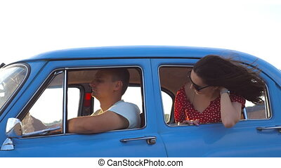 Happy girl in sunglasses leaning out of retro car window and enjoying trip. Young woman looking out window of moving old auto on sunny day. Travel and freedom concept. Slow motion Close up