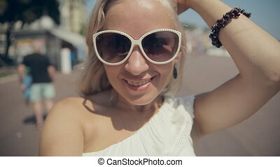 Happy girl in sunglasses takes selfie while walking along...