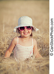 Happy girl in the field of wheat