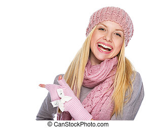 Happy girl in winter clothes pointing on copy space