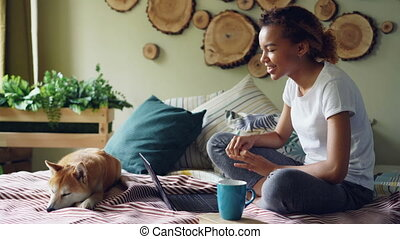 Happy girl is skyping talking online with friends gesturing and looking at laptop screen sitting on bed at home with puppy lying beside her. Communication and technology concept.