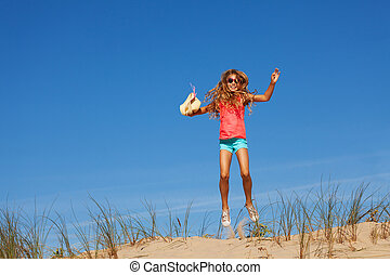Happy girl jump high on the sand dune holding hat