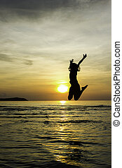 Girl jump welcome sunrise on the beach