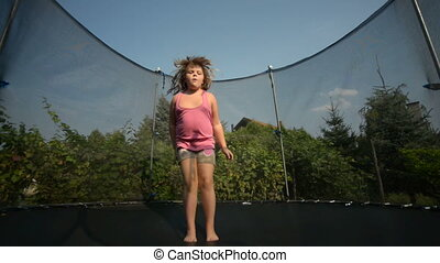 Happy girl jumping in the trampolin