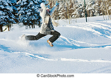 happy girl jumping into snow in winter