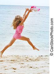 happy girl jumping on sand beach