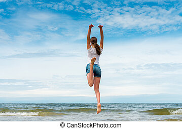 Happy girl jumping on the beach at day time