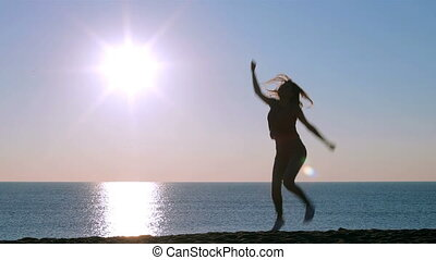 Full body portrait of a happy single excited girl jumping on the beach at sunrise