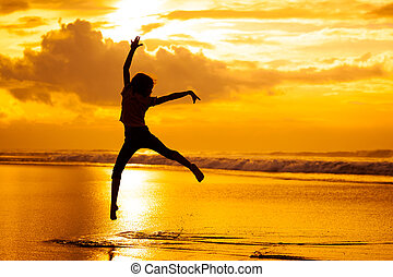 Happy girl jumping on the beach on the dawn time