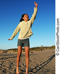 Happy girl jumping on the beach