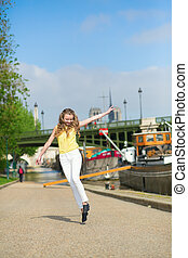 Happy girl jumping on the embankment