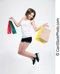 Happy girl jumping with shopping bags