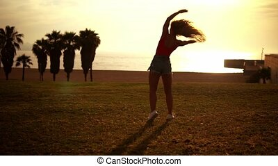 Happy girl jumps and doing cartwheels on beach enjoying...