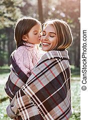 Happy, girl kisses her beautiful mother in forest are covered with blanket