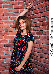 Happy girl leaning on the brick wall