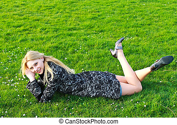 Happy girl lies on a blooming meadow in the early spring morning