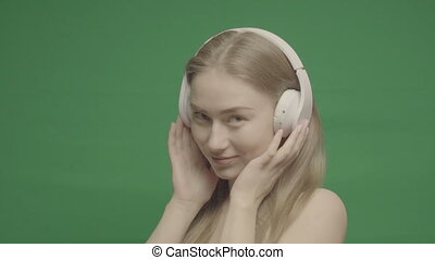 Happy Girl Listen Music in White Headphones and Smiling On a...