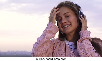 Happy girl listening to music with headphones standing on the roof