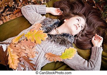 happy girl  lying in autum leaves