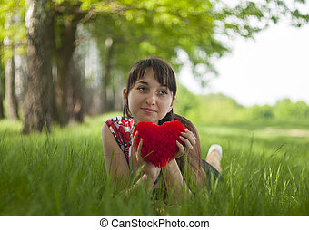 Happy girl lying on the grass with fluffy heart in her hands.