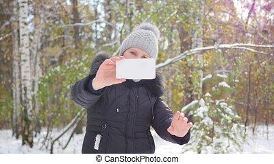 happy girl makes a selfie in winter Park