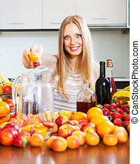 Happy girl making beverages with fruits
