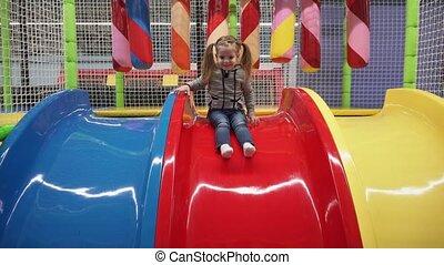 Happy girl moving down slide on playground in children's center