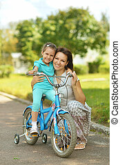 Happy girl on a bicycle with her mother