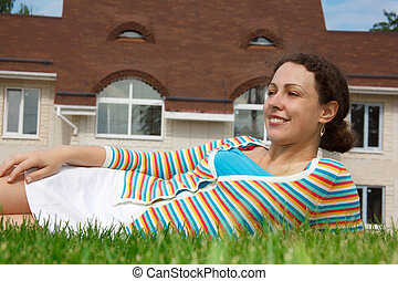 Happy girl on lawn in front of new home. Smiling, she looks into distance. Horizontal format.