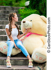 happy girl on the stairs in the park with a huge teddy bear posing
