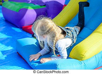 Happy girl on top of giant bouncy slide