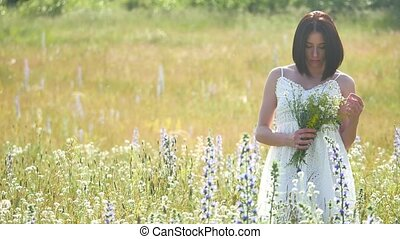 happy girl outdoor in a field with flowers in nature. girl in a field smiling woman holding a bouquet of flowers