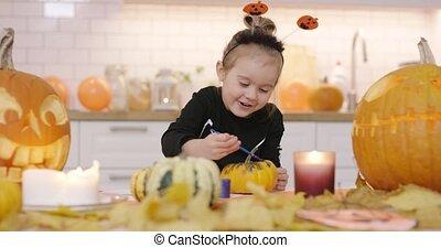 Happy girl painting pumpkin - Little happy-looking girl in...